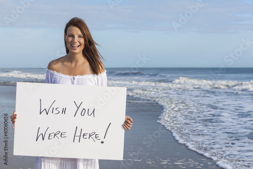 Photo  Woman on Beach Holding Wish You Were Here Card