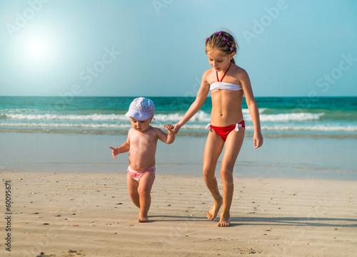 Photo  little sisters walking along the beach
