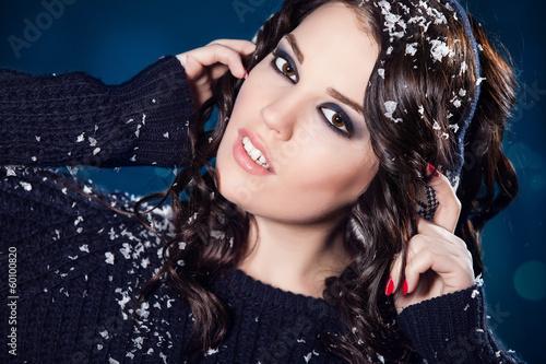 sensual woman enjoying snow. Wearing warm earmuffs