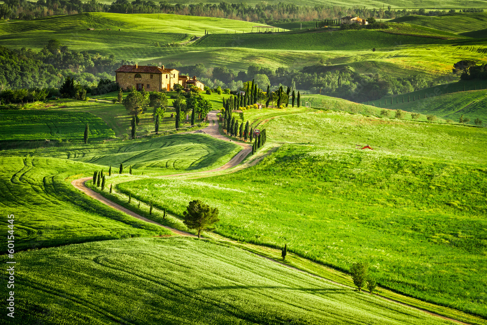 Fototapeta Sunset over farmhouse in Tuscany located on a hill