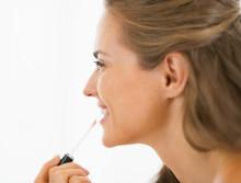 Happy Young Woman Applying Lip Gloss