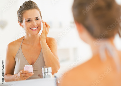 Fototapeta  Happy young woman applying cream in bathroom