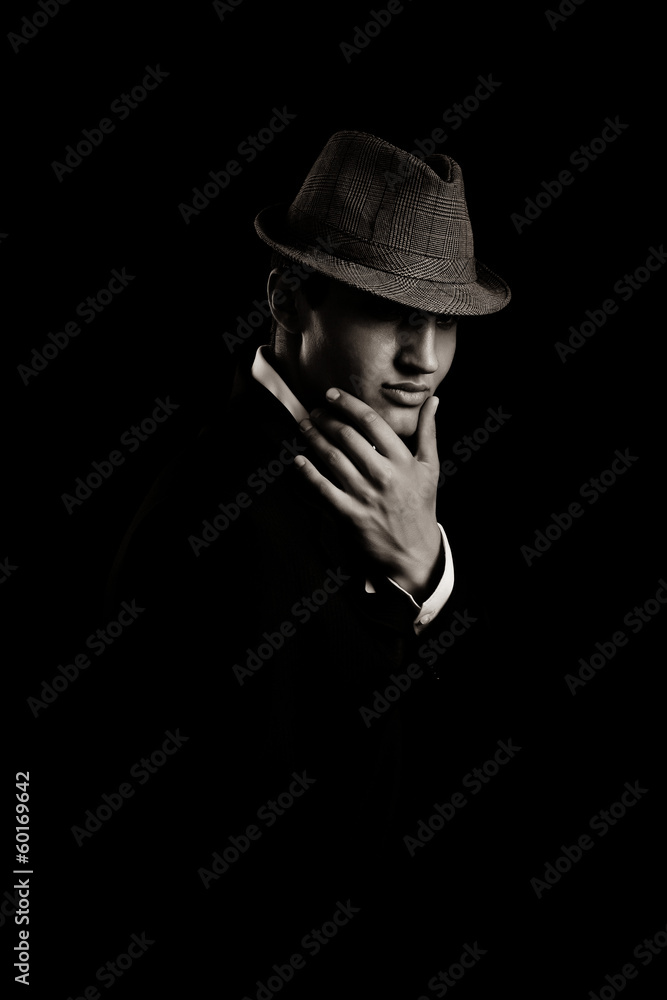 Fototapeta low key portrait of young gangster with hat in the darkness.