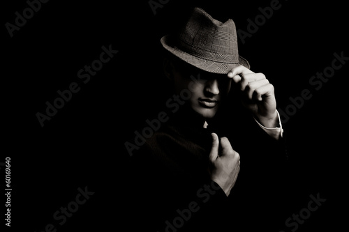 low key portrait of young gangster with hat in the darkness. Tablou Canvas