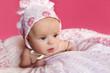 Девочка в чепчике на розовом фоне.