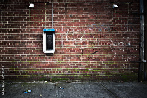 Foto auf Gartenposter Graffiti Grungy urban wall with an old payphone on it