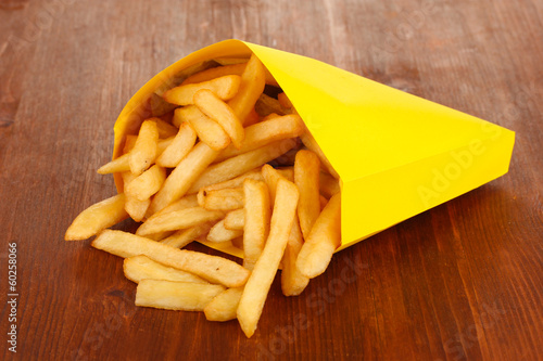 French fries in paper bag on wooden table close-up Poster