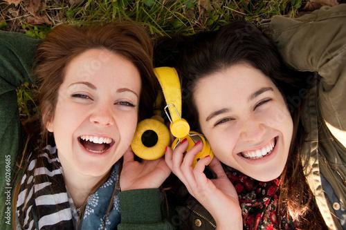 Obraz Happy teen girls sharing music - fototapety do salonu