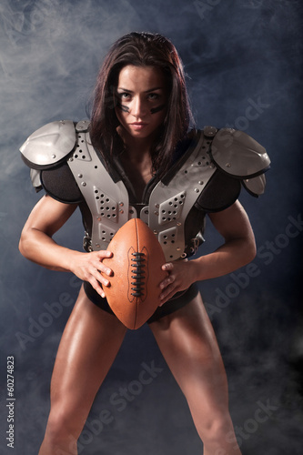 quarterback girl with a ball in the smoke