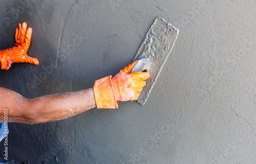 Photo  plasterer concrete worker at wall of house construction