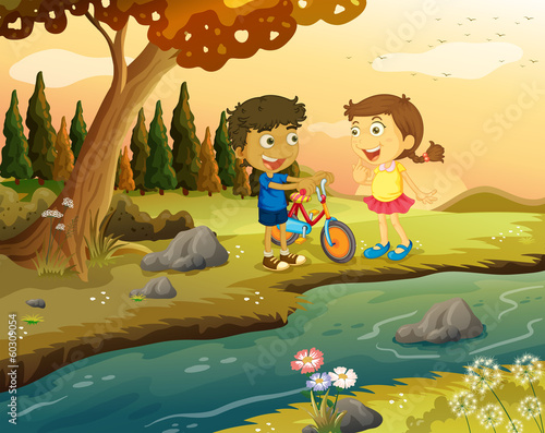 Poster Indiens A boy and a girl with a bike standing at the riverbank
