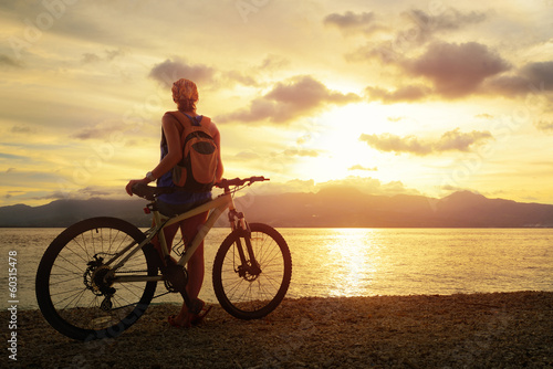 Young woman with backpack standing on the shore near her bicycle