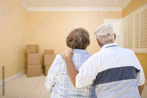 Fotografiet  Senior Couple In Room Looking at Moving Boxes on Floor