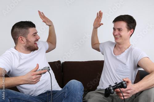 Junge Leute gewinnen beim Spielen auf Spielkonsole плакат