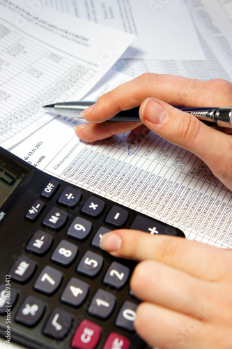 Office table with calculator, pen and accounting document - 60393412