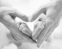 Tiny Newborn Baby's Feet On Fe...