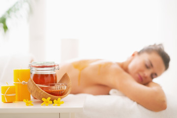 Closeup on honey spa therapy ingredients and woman in background