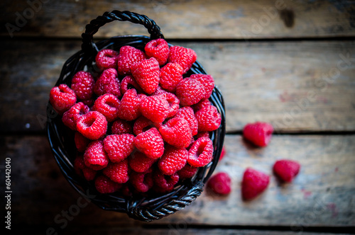 Raspberries in a basket on rustic wooden background Canvas Print