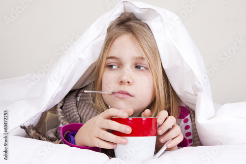 Fotografía  Sick young girl with thermometer in bed