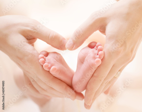 Tiny Newborn Baby's feet on female Heart Shaped hands closeup Poster