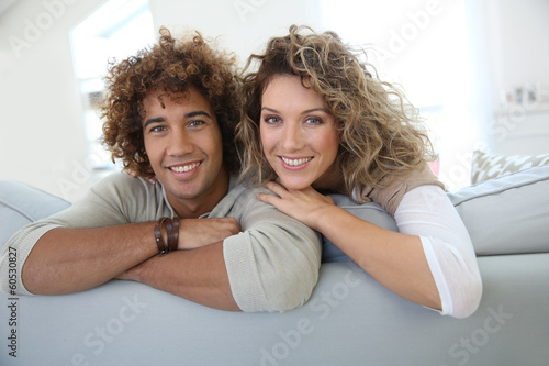 Valokuvatapetti Sweet couple relaxing at home in sofa