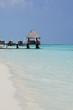 Wooden pier over a white beach in Maldive Islands