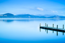 Wooden Pier Or Jetty And On A Blue Lake Sunset And Sky Reflectio