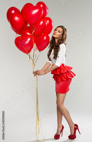 Photo  Beautiful young woman with red balloon heart shape for valentine