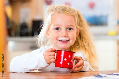 Fotografie, Obraz  Mädchen trinkt Milch in der Küche