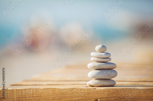 Foto op Aluminium Stenen in het Zand zen stones jy wooden banch on the beach near sea. Outdoor