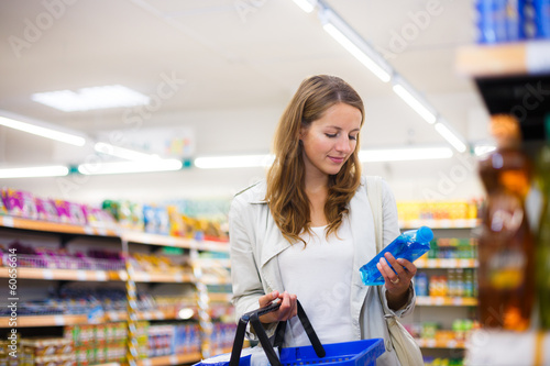Fotografía  Beautiful young woman shopping in a grocery store/supermarket