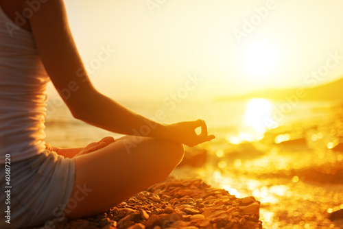 In de dag School de yoga hand of woman meditating in a yoga pose on beach