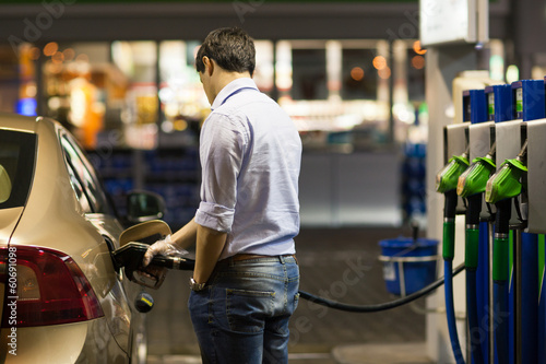 Photo  Young man fueling his car at the gas station