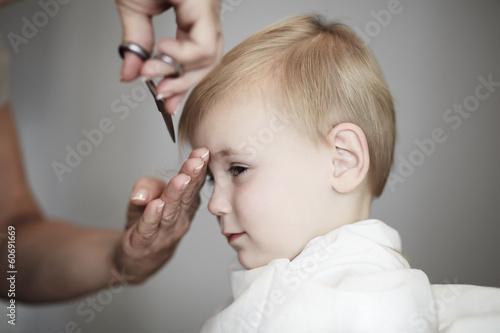 Little girl having her fist time at hairdresser