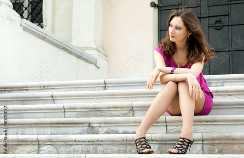 Young Woman Sitting On The Ladder Of Old City