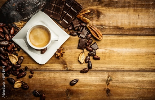 Spoed Foto op Canvas koffiebar Coffee cup on a wooden table among coffee beans