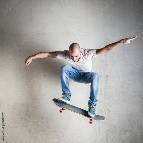 Skateboarder jumping against concrete wall. Canvas-taulu