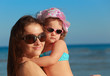 Beautiful happy mother and kid girl on blue sea background