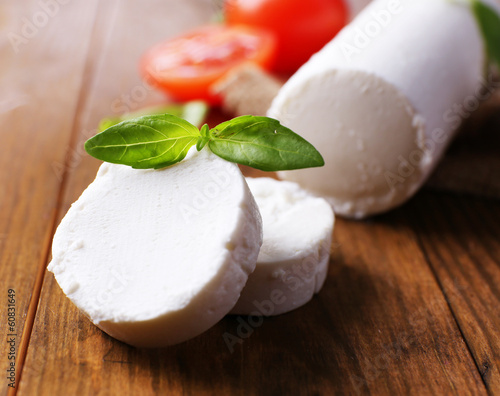 Aluminium Prints Dairy products Tasty bushe cheese with basil and tomato, on wooden table