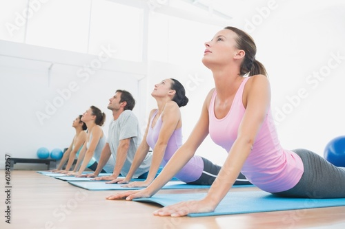 Poster Ecole de Yoga Class exercising in row at fitness studio