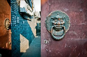 Fototapeta brass lion head door knockers in hutong area in Beijing, China