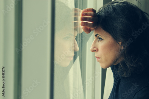 beautiful 35 year old woman stands in front of the window Fototapet