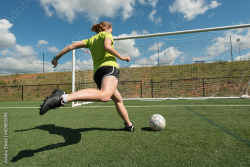 Photo  Female soccer player shooting on goal wide low angle