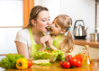 mother feeding kid vegetables in kitchen