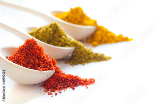Poster Spices Spices in wooden spoons on a white background closeup