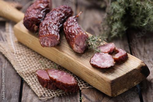 Photo Dried sausage on kitchen plank