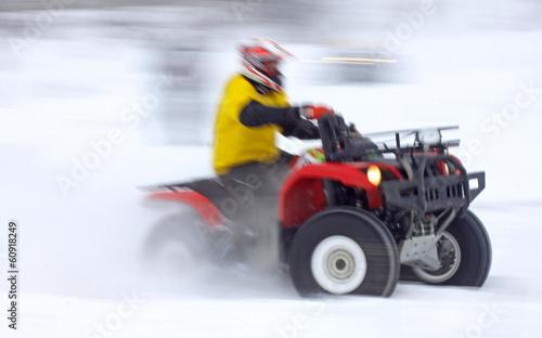 Quad bike driver rides over snow track