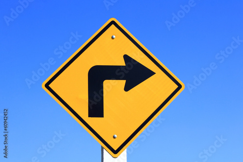 Fotografía  turn right yellow road sign on blue sky background