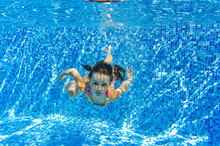 Happy Active Child Swims Underwater In Pool And Have Fun