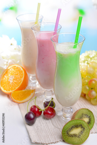 Fototapety, obrazy: Milk shakes with fruits on table on light blue background
